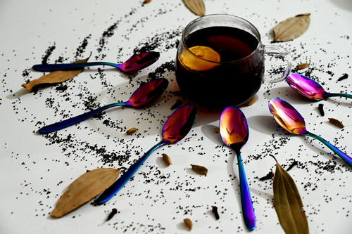 A Cup of Tea Surrounded by Teaspoons