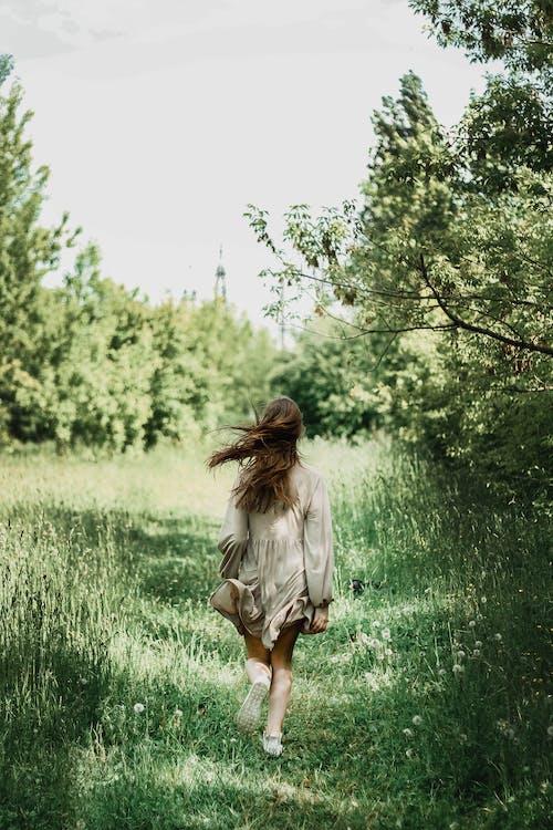 Woman in Gray Dress Walking on Green Grass Field