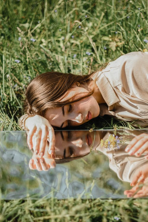 Woman in Brown Long Sleeve Shirt Lying on Green Grass Field
