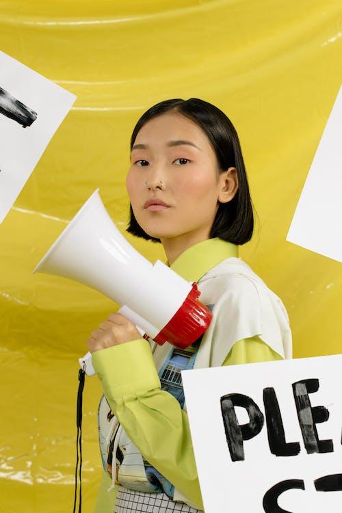 Girl in Yellow and White Long Sleeve Shirt Holding White Ceramic Mug