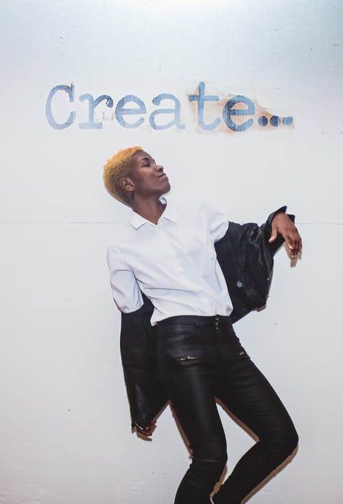 Young trendy African American female in white shirt and leather jacket having fun while looking up under Create title