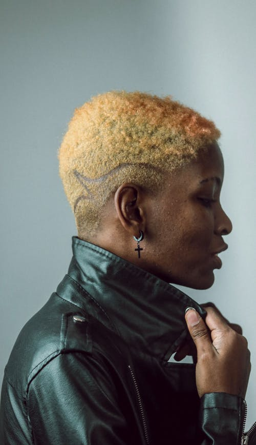 Cool black woman with modern haircut on light background
