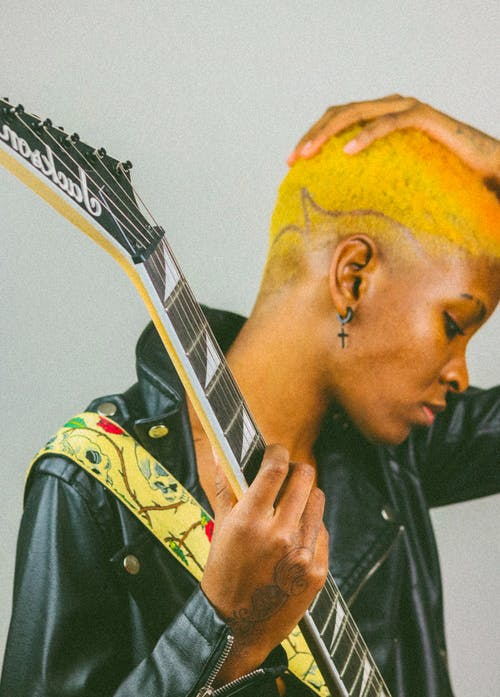 Side view of crop stylish African American female musician with short dyed hair in leather jacket touching head while standing against white background with electric guitar