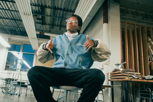 Confident black male teenager showing shaka sign in workshop
