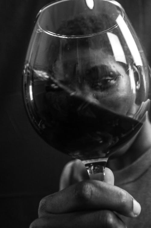Black and white of anonymous African American male drinking wine and looking at camera through glass