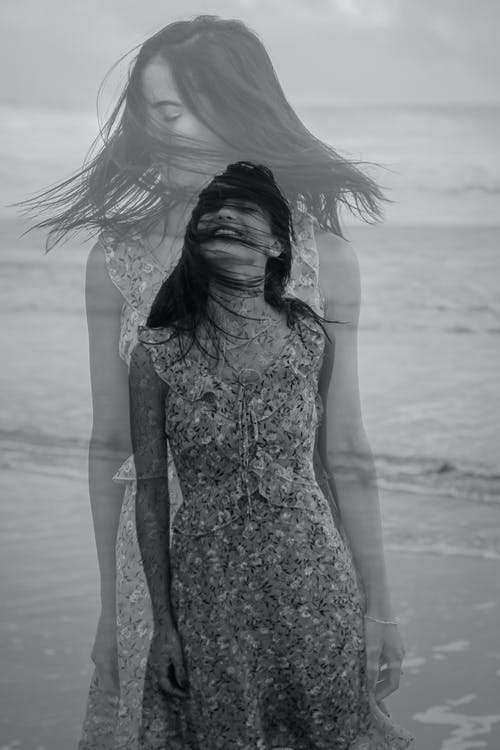 Black and white of young dreamy female tourist in ornamental sundress against wavy sea during summer trip