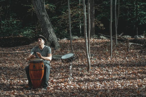 Full body of concentrated middle aged male musician in casual clothes and hat playing conga percussion instrument sitting in autumn park with fallen leaves near drum