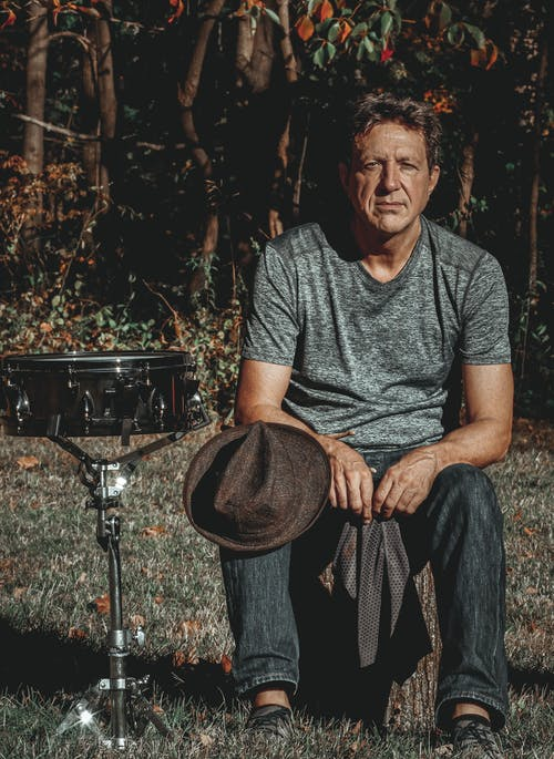 Calm male musician sitting near drum after performance in nature