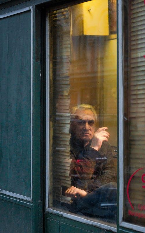 Man in Black and Gray Jacket Sitting Beside Green Wooden Door