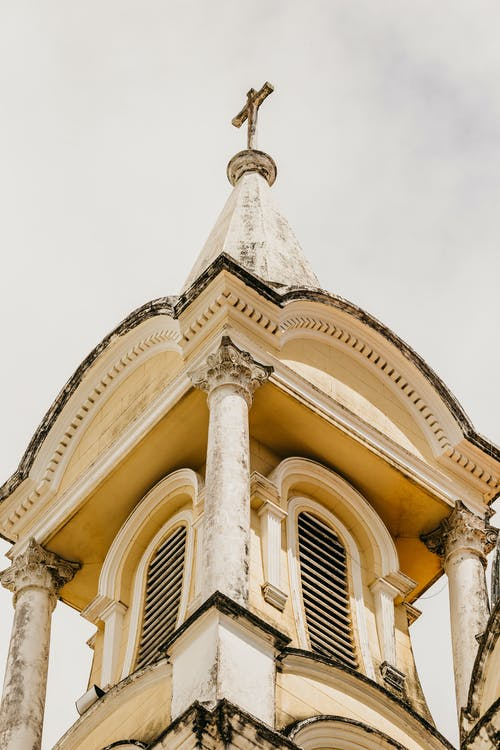 Aged Catholic cathedral with cross on tower