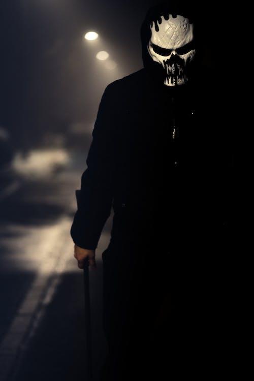 Man in Black Coat Holding Stick