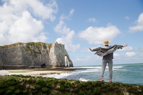Faceless traveler on stony coast near sea