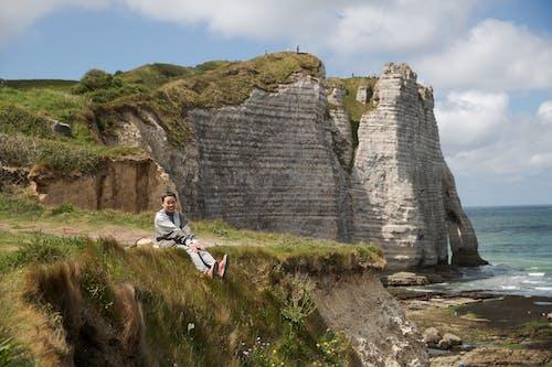 Smiling Asian woman sitting on rocky coast near sea