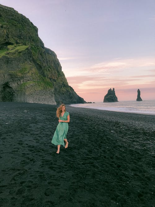 Woman in Teal Dress Standing on Seashore