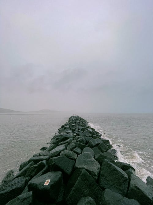 Gray Rocks on Sea Under White Sky