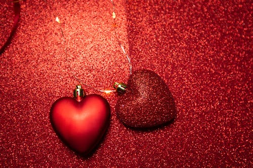 Top view of heart shaped decorations placed on red surface with bright glitters during holiday celebration on Saint Valentine day