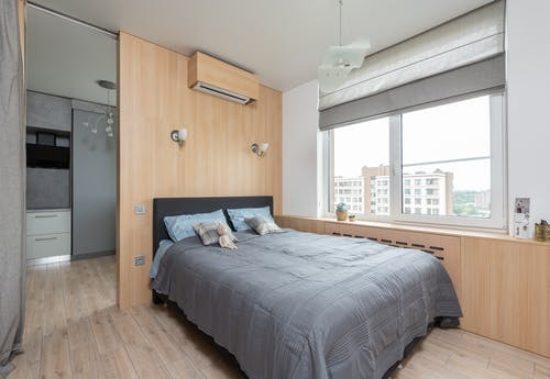 Interior of light modern apartment with bed near window and jalousie with windowsill with decorative elements near air conditioner and entrance to kitchen