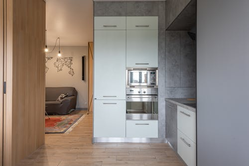 White Top Mount Refrigerator Beside White Wooden Cabinet
