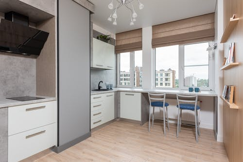 Interior of light kitchen with white cabinets and cupboards with sink and tap near counter with chairs near window with jalousie near shelves with books