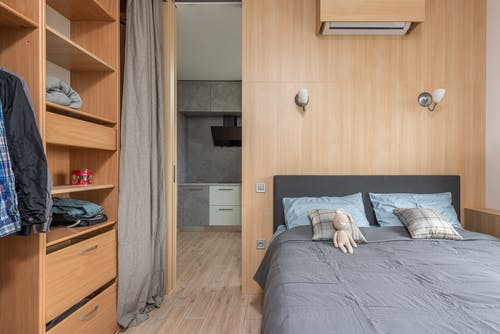 Modern room interior with bed with pillows and soft rabbit toy near wardrobe with shelves and clothes near entrance to kitchen with curtains in light apartment