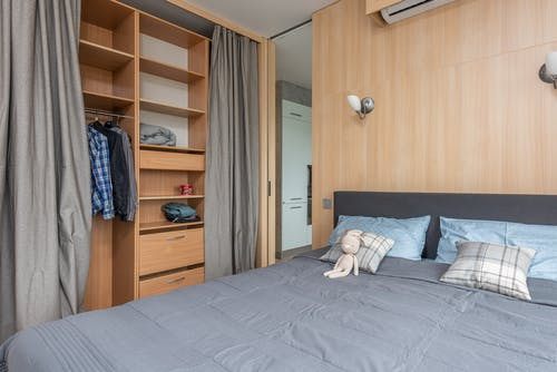 Interior of studio with bed near cupboard with shelves
