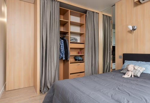 Interior of room with bed near cupboard with shelves