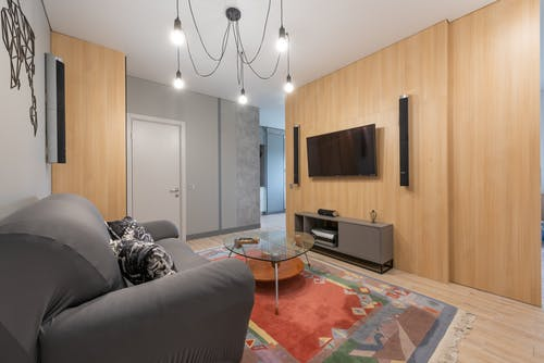 Modern apartment Interior with sofa with pillows near glass table on carpet near cabinet and TV with speakers near lamp on ceiling and door