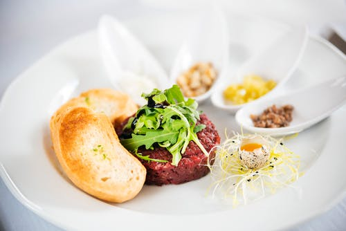 Delicious steak tartare with arugula leaves on plate