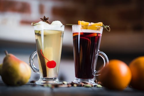 Glasses of mulled wine beverages with froth and fresh orange with pear pieces on top