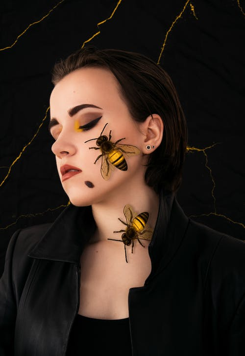 Woman in Black Leather Jacket With Gold and Black Butterfly on Her Face
