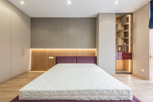 Modern interior design of empty bedroom with cozy king size bed without sheets and empty closets