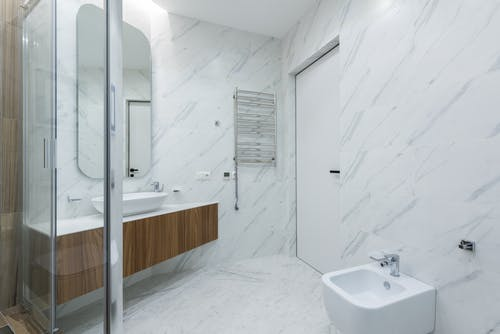 Interior of contemporary spacious bathroom with white sink and mirror placed near closed door against bidet and transparent shower cabin