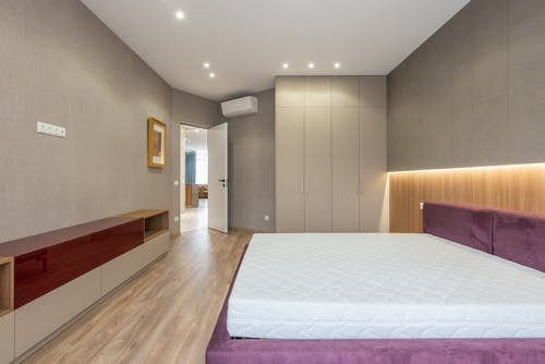 Interior of stylish spacious bedroom with white mattress on bed placed against cupboard near wardrobe and opened door in apartment