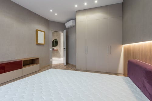 Interior of modern bedroom with white mattress on bed placed against cabinet near big closet and opened door in spacious apartment