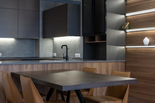 Contemporary black cupboards with sink in stylish kitchen near wooden table and chairs placed near wall with light decoration at home