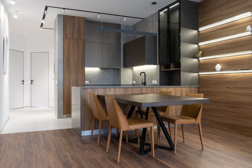 Table and chairs placed near modern kitchen counter with cupboards in stylish apartment with white doors in corridor at home