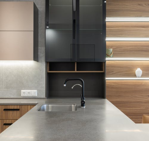 Gray kitchen counter with faucet and sink near cabinets and light decorations on wooden wall in modern apartment at home