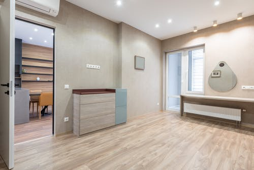Interior of spacious light room with opened door and cupboard placed near glass entrance door in modern apartment with mirrors