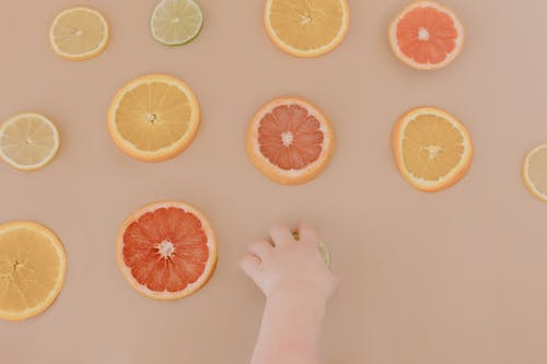 Sliced Citrus Fruits on Brown Surface
