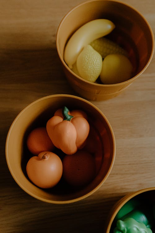 From above of colorful realistic toy fruits and vegetables placed in bowls on wooden table