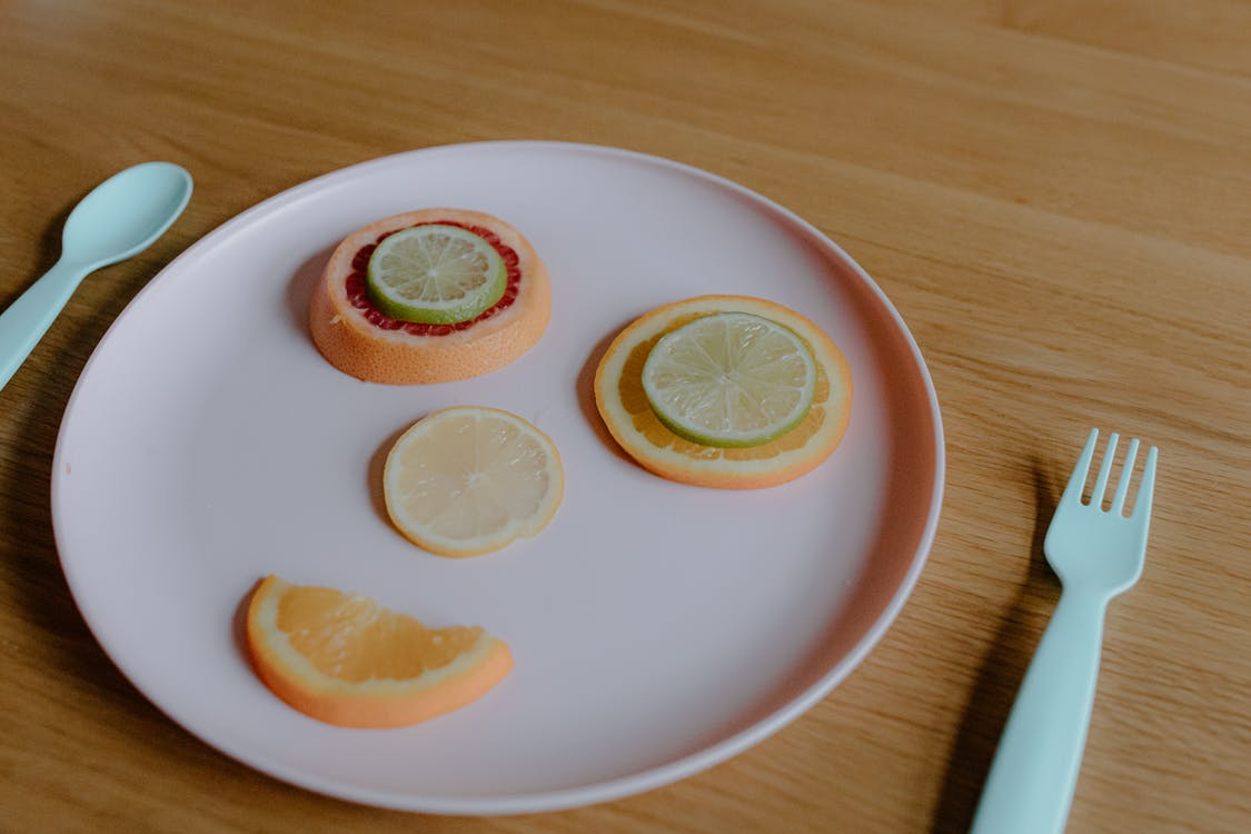 Multicolored citrus fruit creating funny face on plastic plate