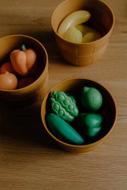 High angle of assorted multicolored toy veggies and fruits stacked in plastic pots placed on wooden table