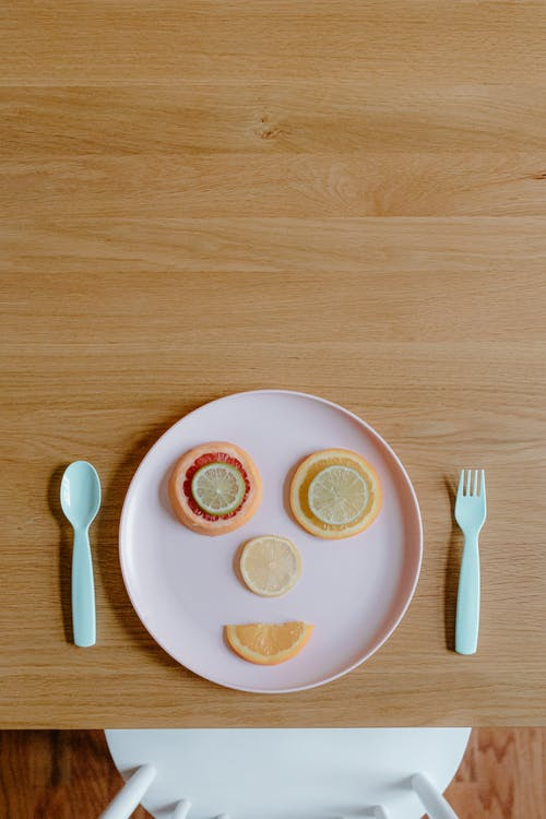 Funny face created by assorted sliced fruits on plastic plate