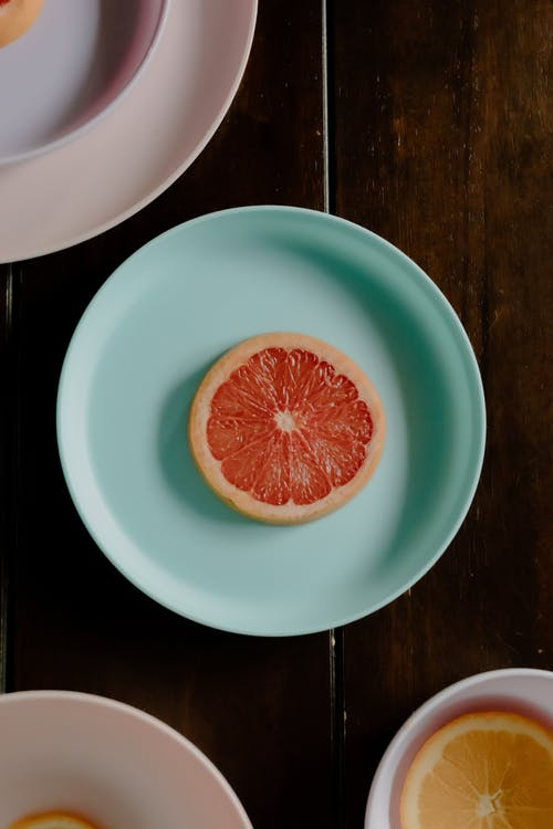 Plates with citrus fruits on table