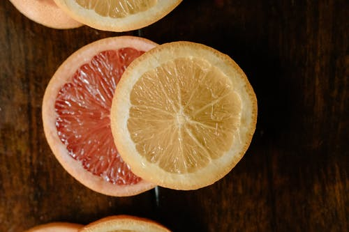 Top view of texture of pulp of sliced grapefruit and lemon on wooden table