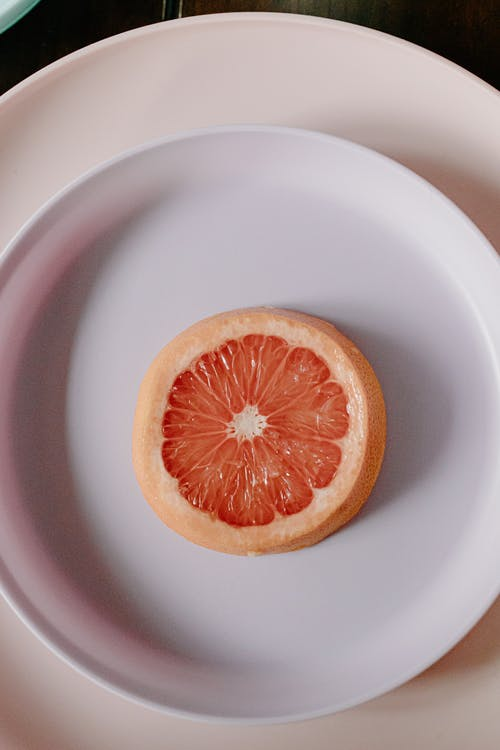 Plate with slice of fresh juicy grapefruit
