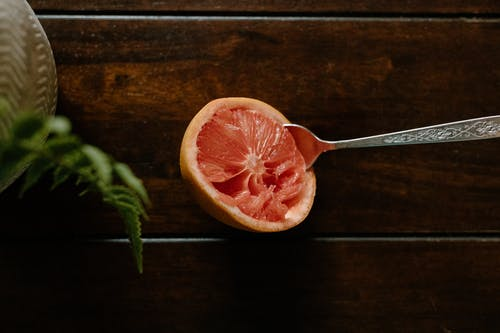 High angle of sour grapefruit with spoon in bright pulp placed on wooden table near plant in vase