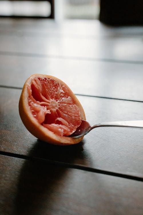 Half of juicy grapefruit with spoon