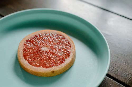 Sliced juicy grapefruit on plate on wooden table