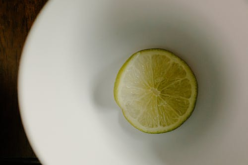 Top view of slice of green lime in plastic bowl for healthy dish